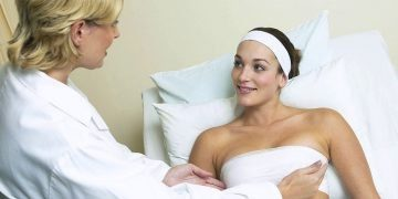 Woman having a breast lift with implants